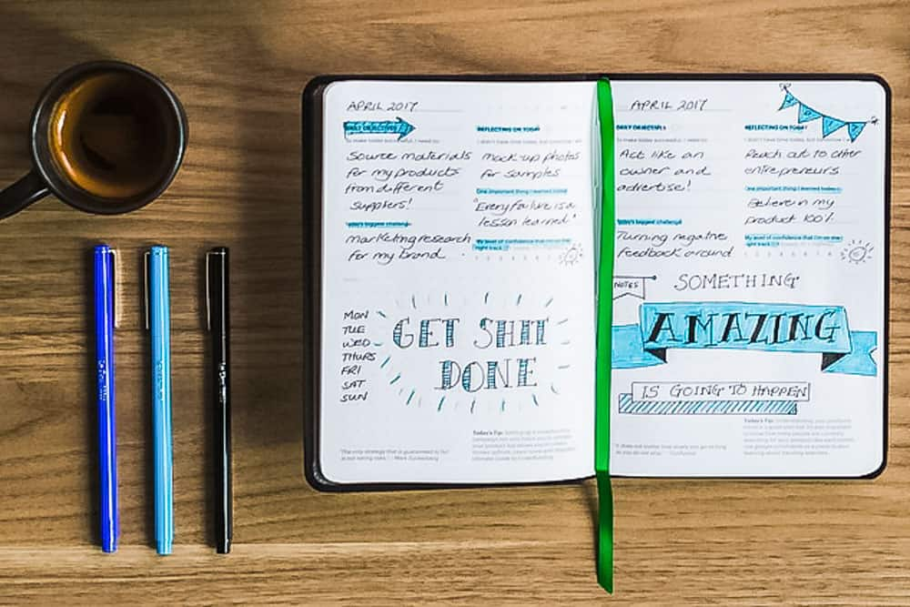 bullet journal laid out on wooden desk with pens and coffee