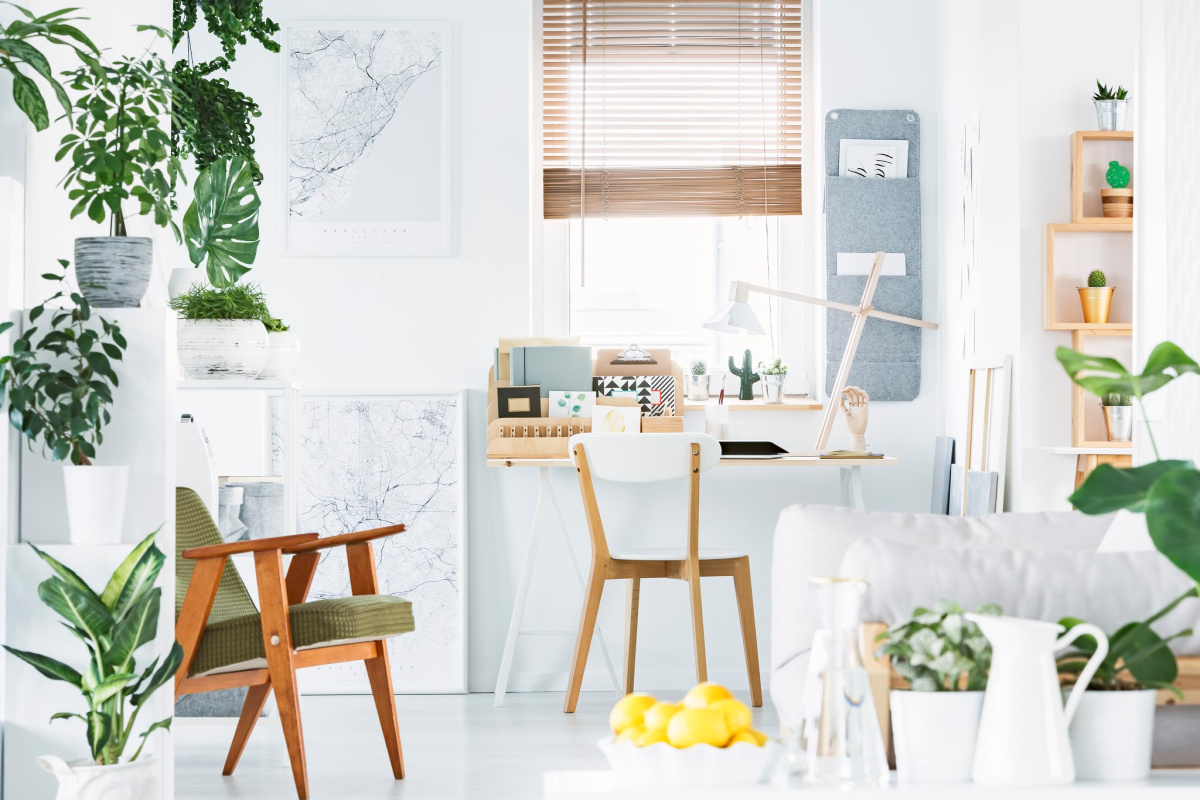 Creative home office interior with a retro armchair, desk, window, plants and bowl of yellow fruit