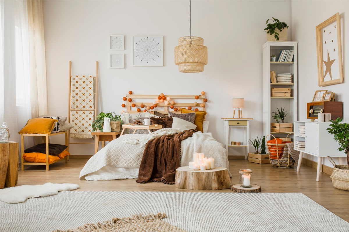 Brown blanket on bed in spacious hygge bedroom interior with bright carpet and posters on white wall