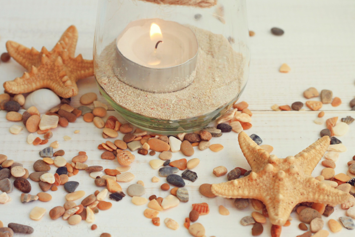 Tea light candle in jar with sea sand. Framed pebbles, starfish.Summer beach style home decor.
