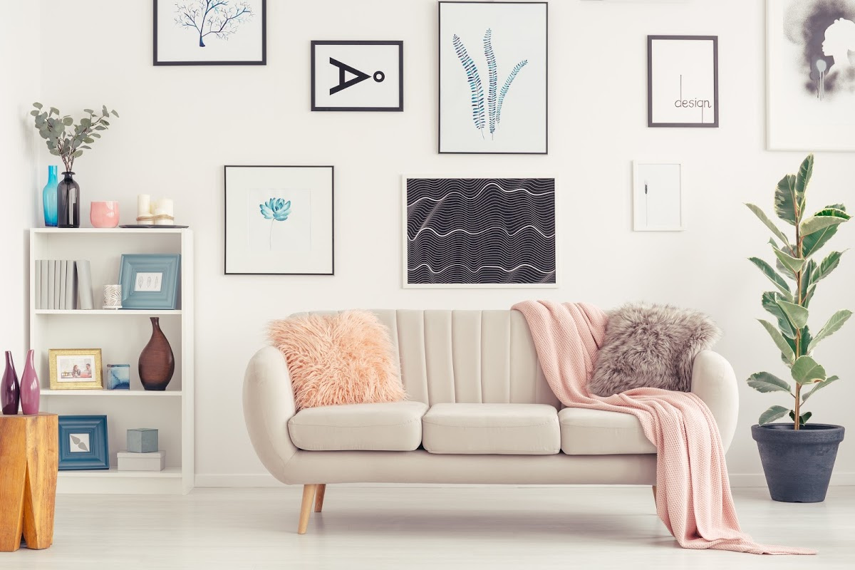 Elegant sofa, white shelf with decorations and posters on the wall in a living room interior