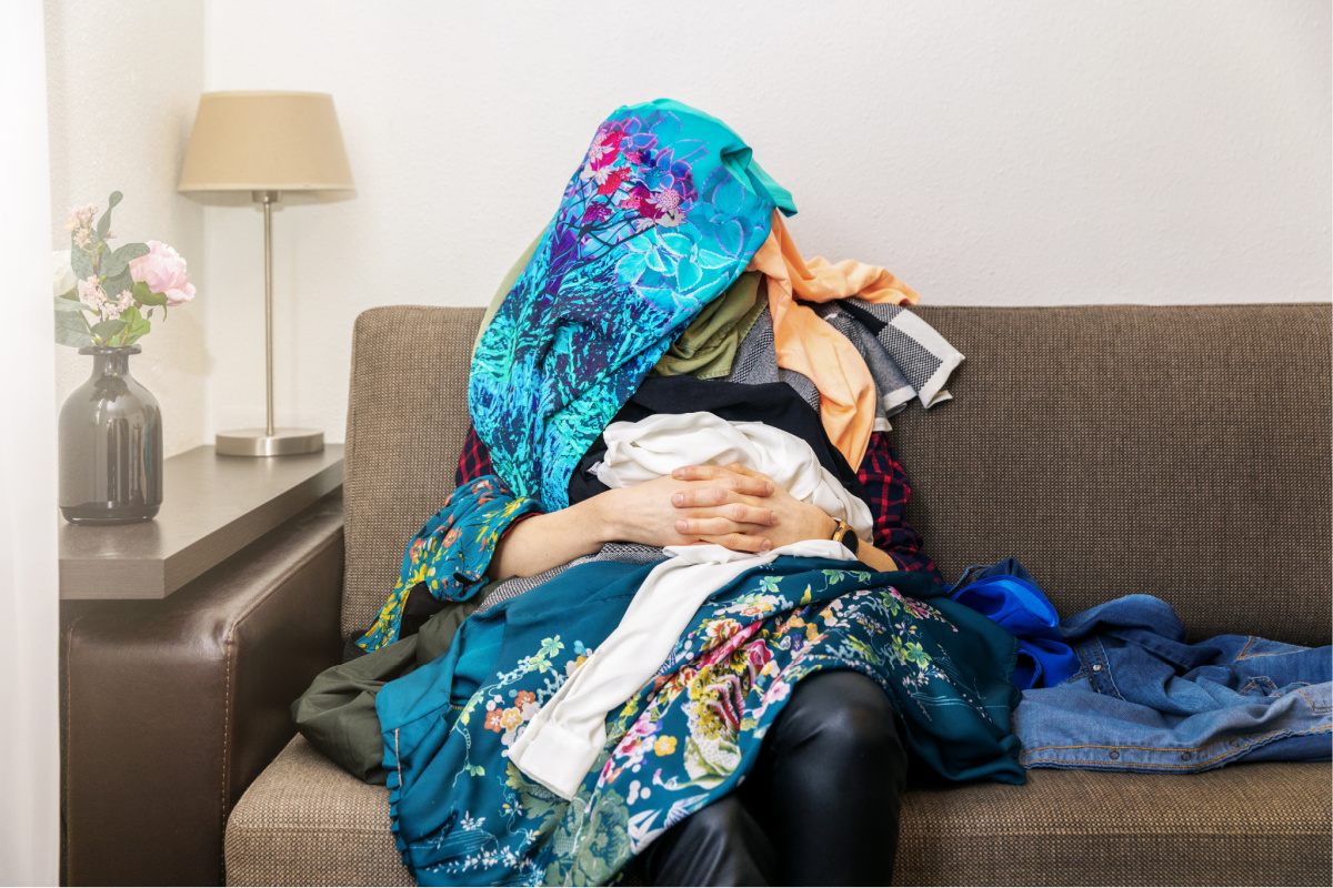 greedy shopping obsessed woman sitting on couch with clothes heap on her