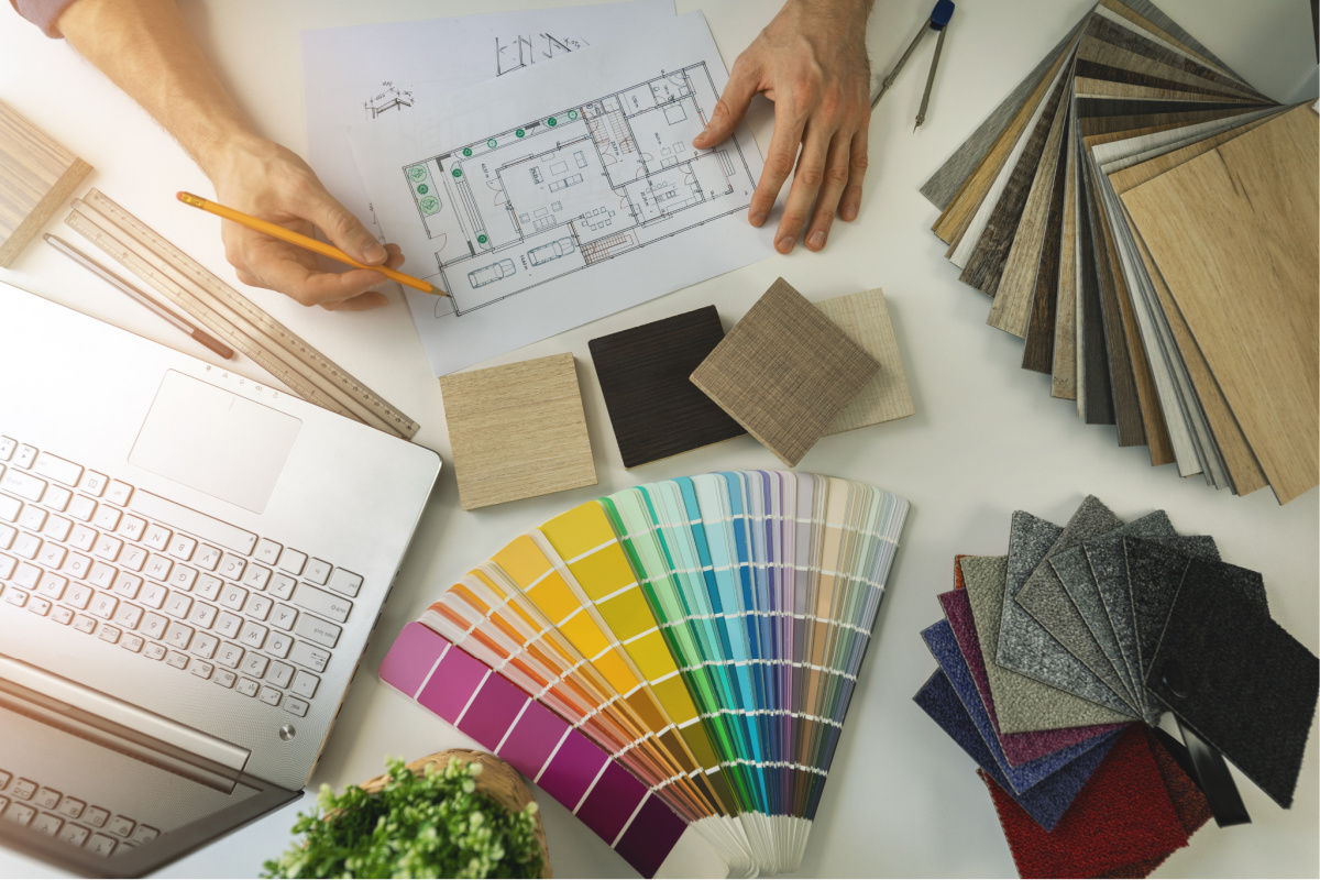 designer working in office doing furniture and flooring material selection from samples for home interior design project. top view